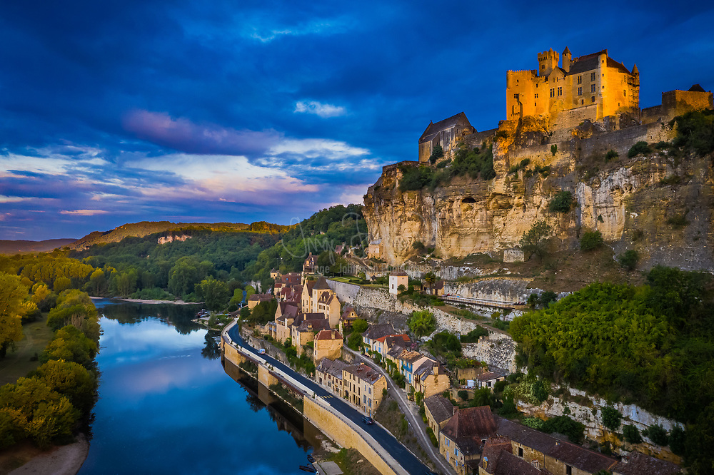 The Château de Beynac is a castle situated in the commune of Beynac-et-Cazenac, in the Dordogne département of France. The castle is one of the best-preserved and best known in the region.<br /> <br /> This Middle Ages construction, with its austere appearance, is perched on top of a limestone cliff, dominating the town and the north bank of the Dordogne River. The castle was built in the 12th century by the barons of Beynac (one of the four baronies of Périgord) to close the valley. The sheer cliff face being sufficient to discourage any assault from that side, the defences were built up on the plateau: double crenellated walls, double moats, one of which was a deepened natural ravine, double barbican.<br /> <br /> The oldest part of the castle is a large, square-shaped, Romanesque keep with vertical sides and few openings, held together with attached watch towers and equipped with a narrow spiral staircase terminating on a crenellated terrace. To one side, a residence of the same period is attached; it was remodelled and enlarged in the 16th and 17th centuries. On the other side is a partly 14th century residence side-by-side with a courtyard and a square plan staircase serving the 17th century apartments. The apartments have kept their woodwork and a painted ceiling from the 17th century. The Salle des États (States' Hall) has a Renaissance sculptured fireplace and leads into a small oratory entirely covered with 15th century frescoes, included a Pietà, a Saint Christopher, and a Last Supper in which Saint Martial (first bishop of Limoges) is the maître d'hôtel.<br /> <br /> At the time of the Hundred Years' War, the fortress at Beynac was in French hands. The Dordogne was the border between France and England. Not far away, on the opposite bank of the river, the Château de Castelnaud was held by the English. The Dordogne region was the theatre of numerous struggles for influence, rivalries and occasionally battles between the English and French supporters. However, the castles fell more of