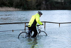 © Licensed to London News Pictures. 01/02/2014; Bristol, UK.  Cyclists on a flooded cycle path by the river Avon and Cumberland Road.  Nearby a portable flood barrier was set up in Avon Crescent near Bristol docks to protect a row of houses from spring tide flooding from the river Avon.  01 February 2014.<br /> Photo credit: Simon Chapman/LNP
