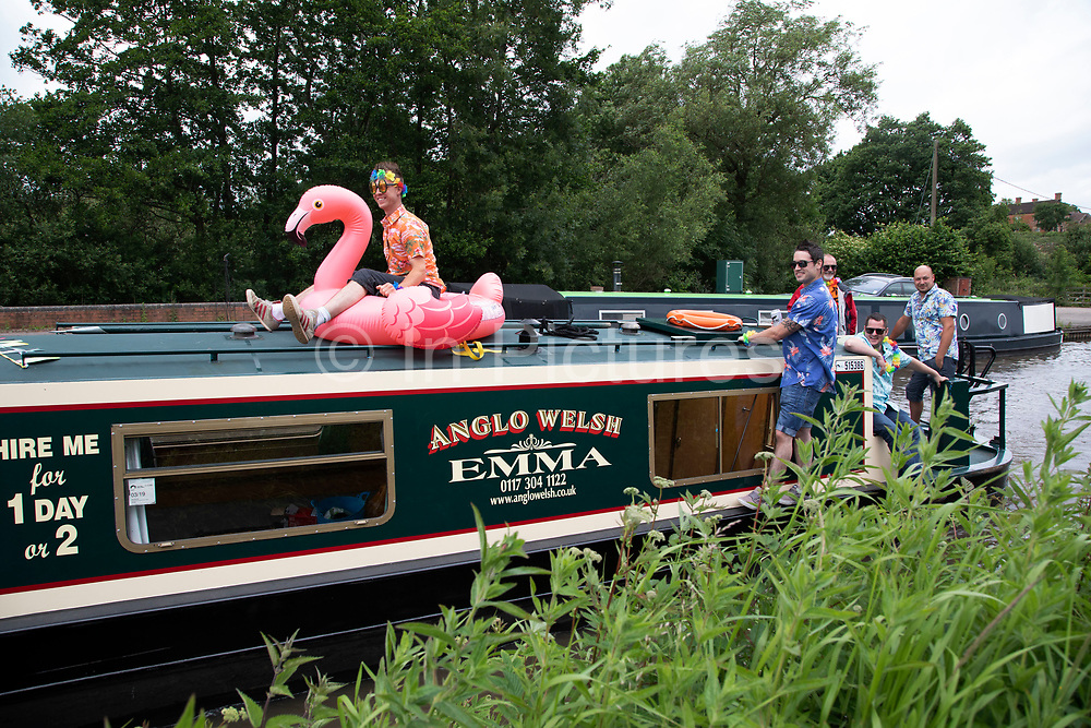 Day trippers wearing Hawaiian shirts on a narrowboat enjoy the festivities of a party on a canal near Alvechurch, United Kingdom.