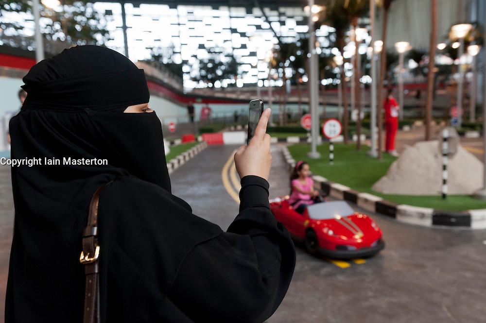 Woman in black abaya photographs child at Ferrari World theme park in Abu Dhabi UAE United Arab Emirates
