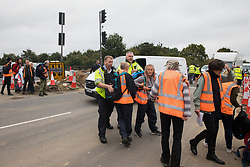 Enfield, UK. 15th September, 2021. Metropolitan Police officers ask Insulate Britain climate activists to move out of a slip road from the M25 at Junction 25 to allow ambulances to pass after it was blocked as part of a campaign intended to push the UK government to make significant legislative change to start lowering emissions. The activists, who wrote to Prime Minister Boris Johnson on 13th August, are demanding that the government immediately promises both to fully fund and ensure the insulation of all social housing in Britain by 2025 and to produce within four months a legally binding national plan to fully fund and ensure the full low-energy and low-carbon whole-house retrofit, with no externalised costs, of all homes in Britain by 2030 as part of a just transition to full decarbonisation of all parts of society and the economy. Credit: Mark Kerrison