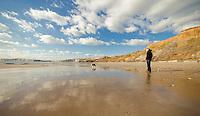 Young man walking the Dog on Compton Beach, Isle of Wight