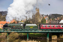 """© Licensed to London News Pictures. 09/04/2018. Ruswarp UK. The 1934 Steam Locomotive 926 """"Repton"""" travels across the River Esk in the village of Ruswarp in The North Yorkshire Moors this morning on it's way from Whitby to Pickering. The engine built in 1934 & Known as Repton was built in Eastleigh & designed by Richard Maunsell, it is known as a SR Class V """"Schools"""" & worked the Southern Railway & British Railways lines. Photo credit: Andrew McCaren/LNP"""
