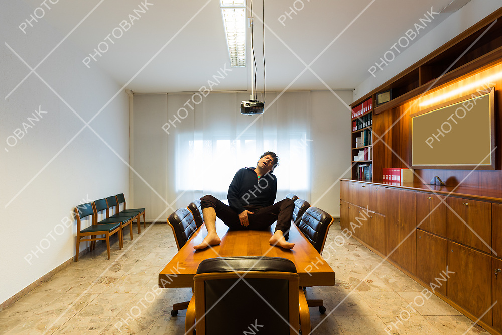 Lonely man in the meeting room in madness gestures