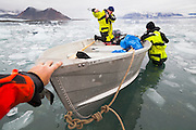 Glaciologist Jacek Jania starts the outboard motor as Jaroslaw Halat and Ethan Welty stabilize the boat on the ice choked beach at the Polish Polar Station in Hornsund, Svalbard.