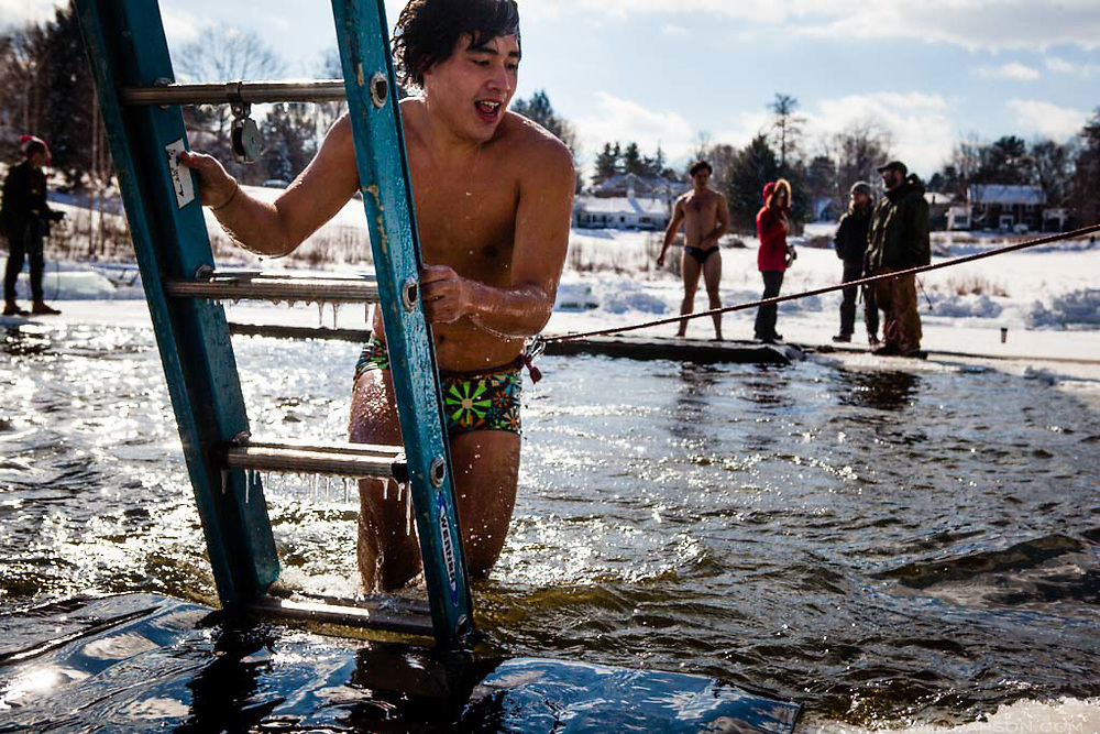 """Dartmouth College senior Ben Weill of New Haven, Conn., emerges from Occom Pond in Hanover, N.H., during the Dartmouth Winter Carnival Polar Bear Swim on February 7, 2014. Weill, who in four years at Dartmouth had never done the swim at Occom, said he and his friends were checking it off their """"bucket list."""" (Valley News - Will Parson)"""