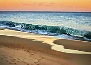 Play of sun and sky at dusk on a beach in Rhode Island.