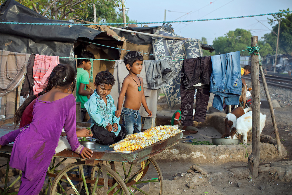 A boy, surrounded by some young friends, is selling corn from his family's cart, parked along the railway tracks in New Arif Nagar, one of the water-affected colonies standing next to the abandoned Union Carbide (now DOW Chemical) industrial complex, site of the infamous 1984 gas tragedy in Bhopal, Madhya Pradesh, central India. The poisonous cloud that enveloped Bhopal left everlasting consequences that today continue to consume people's lives.