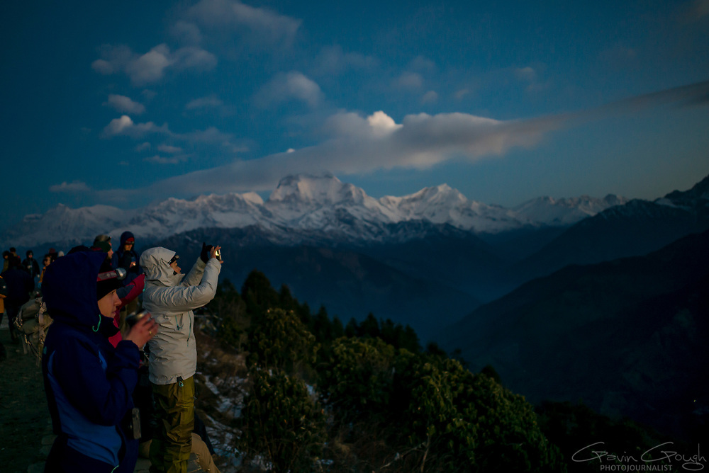 Tourists and trekkers gather at Poon Hill at dawn to see the sun rise over Dhaulagiri and the Annapurna Massif, Poon Hill, Ghorepani, Nepal