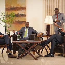 Quatro senhores a conversarem sobre negócios numa sala de estar. Angola