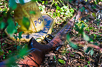 A powerful hunting rifle that was recovered during a contact with poachers lies on the ground and is marked by a police cone. Careful evidence collection is required at each incident to be used in criminal proceedings against the poachers.