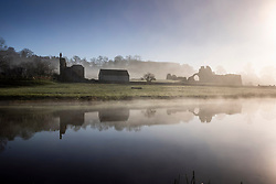 © Licensed to London News Pictures. 22/03/2021. Whitby UK. The ruins of Kirkham Abbey reflect into the River Derwent as the sun burns of the early mist this morning. Photo credit: Andrew McCaren/LNP