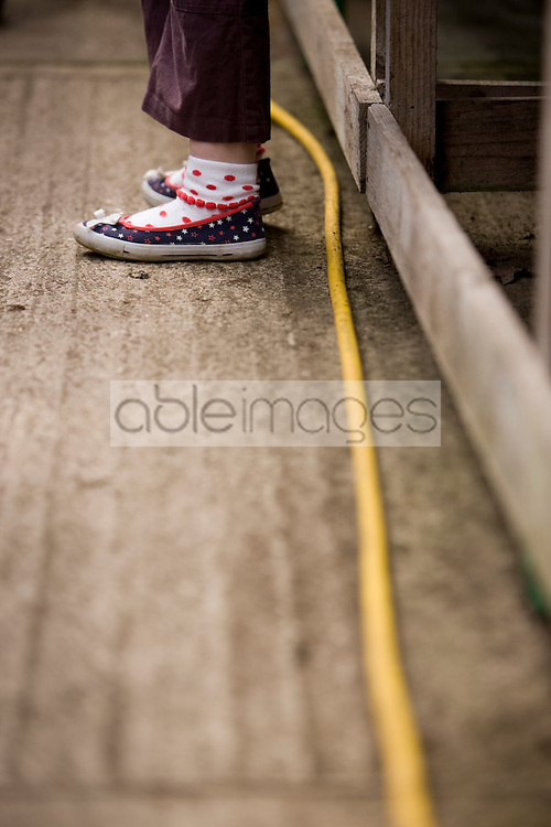 Close up of young girl feet and garden hose