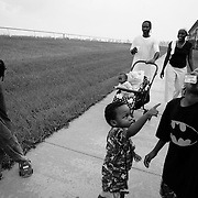 """PALM BEACH, FL - September 6, 2005: .Families and their children at the Palm Meadows complex in West Palm Beach, Florida on September 6, 2005...The Johnson Family:  Father is Kevin Johnson, 38, wife is Michelle Johnson, 27, daughter My-Shelle, 8, son Kevin the 3rd (nickname """"Ope""""), 7, son Kevin the 4th (nicknamed """"Old Man""""), 5, Kevin the 5th (Nickname """"Little Kevin""""), 2 and baby in stroller is I-Shelle, 7 months. The family is walking and playing a game called Under the Bridge.....Family outside their room is Rosa Angelatta, her daughter Sandra Smith (in red) and her grandson, Kenneth, 11, playing with Sandra's niece, Eleanora, 5...Girl with large Tweety Bird doll: Chelsea Gair, 7, walking to her room with stuffed Tweety Bird. They evacuated from New Orleans."""