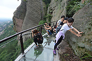 YUEYANG, CHINA - MAY 27: (CHINA OUT)<br /> <br /> Hitting the high notes! China unveils another terrifying glass walkway... and this one is also a giant KEYBOARD that plays musical notes as you walk<br /> <br /> Terrifying 'skywalks' have become a popular activity for Chinese tourists seeking a thrill.<br /> But now local authorities in Hunan province have built the country's first glass walkway that plays music as you walk, in an attempt to soothe the fears of visitors.<br /> The path, which is built along the edge of a cliff nearly 1,000 feet above ground, doubles up as a giant keyboard by responding to footsteps,<br /> Tourists have already been pictured walking tentatively down the 180-metre long glass bottomed path, which is sure to get stomachs churning.<br /> However, those brave enough to get up there are treated topanoramic views of the whole of Pingjiang County, designated an area of outstanding natural beauty.<br /> The walkway consists of two layers of 12mm thick glass glued together and electronic components can respond to footsteps with 70 different notes.<br /> The interactive path in the Shiniuzhai National Park is the first of its kind, although glass walkways appear to be cropping up all across the country recently.<br /> Last month the construction of a walkway in the same scenic spot received widespread attention online after workers were picture walking precariously along wooden planks at the edge of a cliff thousands of feet in the air.<br /> Pingjiang is already very popular with tourist for its Mufu Mountain range and the national park attracts thousands of visitors every year.<br /> Local authorities have been trying to attract even more tourists by building a series of winding mountain paths and glass walkways in the region.<br /> ©Exclusivepix Media