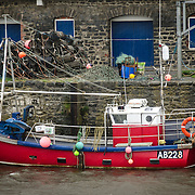 A red fishing trawler moored to the dock during a storm in Aberystwyth on the western coast of Wales.