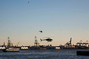 Helicopters fly close to the East River at dusk near the Downtown Manhattan/ Wall Street Heliport; Pier 6, Manhattan, New York City, New York, United States of America.