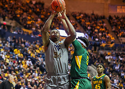 Mar 7, 2020; Morgantown, West Virginia, USA; West Virginia Mountaineers forward Oscar Tshiebwe (34) shoots against Baylor Bears forward Flo Thamba (0) during the first half at WVU Coliseum. Mandatory Credit: Ben Queen-USA TODAY Sports