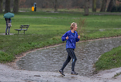 © Licensed to London News Pictures. 03/02/2021. London, UK. A runner braves the rain and flooding on Wimbledon Common in South West London this morning. More rain and flooding has hit the South East today with flooding in Windsor and Oxfordshire as the Met Office issue weather warnings for rain and snow until Monday. Photo credit: Alex Lentati/LNP