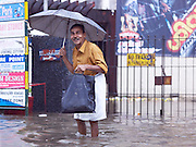 Man with umbrella in a flooded street scene during the monsoon season, Cochin, Kerala, India