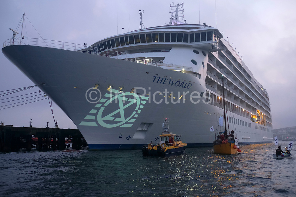 A new Climate Change movement, Ocean Rebellion protest in Falmouth Harbour in Cornwall on the 11th August 2020 in Falmouth, United Kingdom. At sun down the group projected slogans on the bow of the Cruise ship The World. The action was a precursor to the official launch of Ocean Rebellion which is happening on the 19th of August and featured over 40 protestors who took to the water with flags and banners. Demonstrators then projected films and slogans onto the hull of the ship, including Sort your Ship out! and Turn The Tide, to raise awareness of the environmental impact of cruise shipping. The grassroots activist group calling itself Ocean Rebellion, has pledged an escalation of activities throughout the world to protect our common ocean heritage. 'The fuel this ship burns is 100 times more polluting than the fuel we allow on roads. This is having a huge environmental impact not just on the oceans and their ecosystems but on air quality in the coastal communities visited by these ships. Each apartment on this cruise ship has a hundred times more emissions than the average European land based equivalent. That's 380,309kg CO2 per year – that's the weight of a Boeing 747 airplane' When idling in port this ship produces more sulphur pollution than 5,000,000 cars or 138,500 trucks.