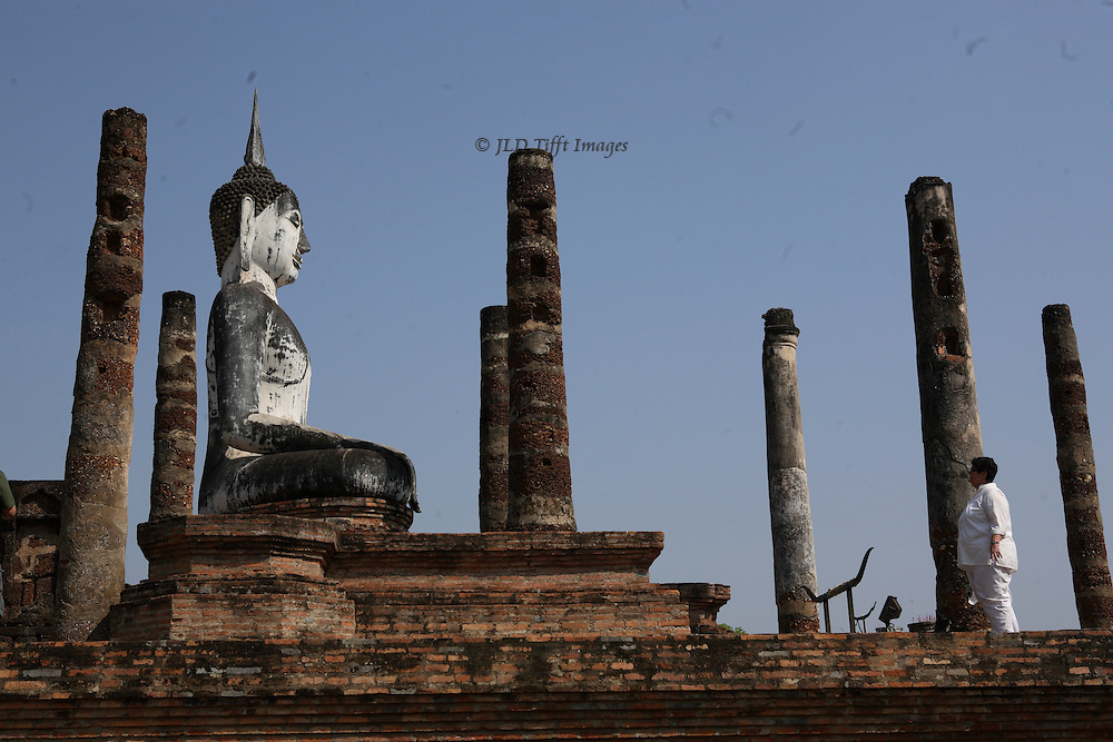 Wat Mahathat, Sukhothai, side view, with a woman visitor contemplating the white Buddha statue from among the truncated columns.
