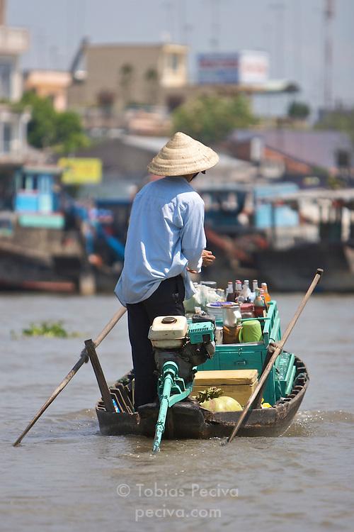 Vendor in his boat, selling beverages at a floating market in the Mekong Delta, Vietnam.