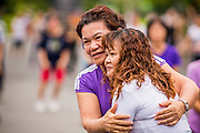 06 OCTOBER 2012 - BANGKOK, THAILAND: Women hug during an exercise class in Lumphini Park in Bangkok. Lumphini Park is 142 acre (57.6-hectare) park in Bangkok, Thailand. This park offers rare open public space, trees and playgrounds in the congested Thai capital. It contains an artificial lake where visitors can rent boats. Exercise classes and exercise clubs meet in the park for early morning workouts and paths around the park totalling approximately 1.55 miles (2.5 km) in length are a popular area for joggers. Cycling is only permitted during the day between the times of 5am to 3pm. Smoking is banned throughout smoking ban the park. The park was created in the 1920's and named after Lumbini, the birthplace of the Buddha in Nepal.   PHOTO BY JACK KURTZ
