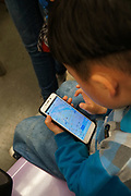 A child learning how to use maps and other useful programs whilst on the underground metro train. Shanghai