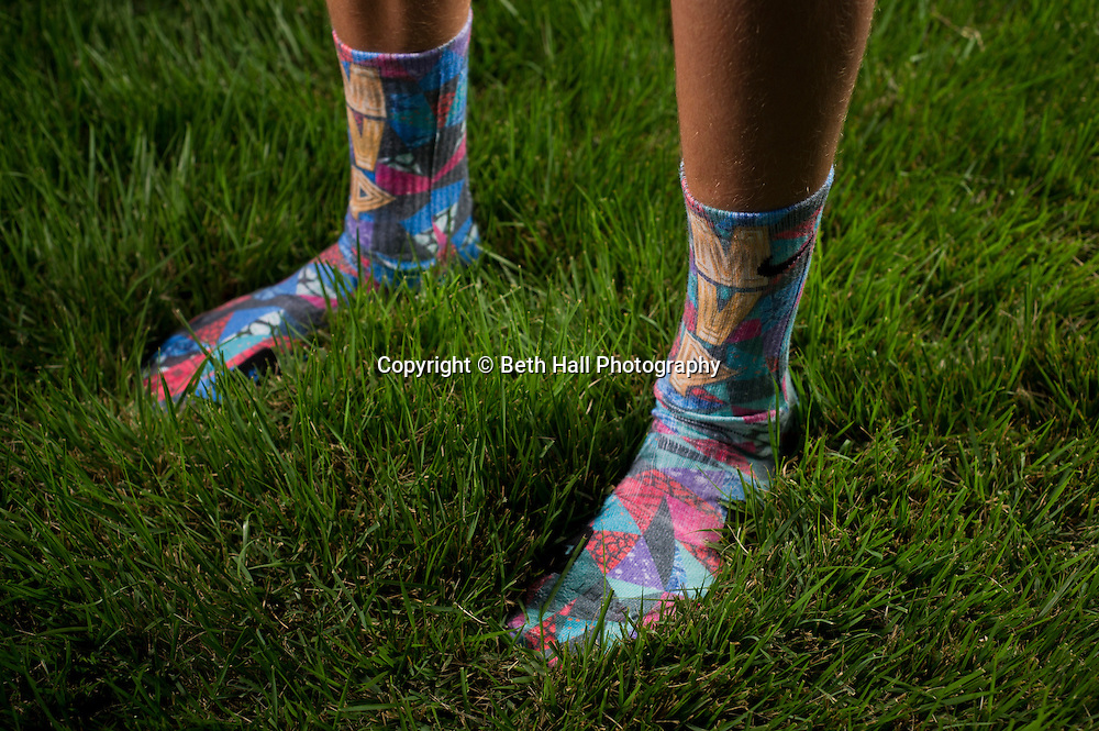 """Winston Robson, 15, of Bentonville, Ark., shows a pair of his sock made by Rock """"Em Apparel while walking through his yard on Tuesday, Sept. 10, 2013, in Bentonville, Ark. Robson owns several pair of the custom Nike Elite socks. Photo by Beth Hall"""