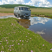 MONGOLIA.   Four-wheel drive van splashes through stream in southern Darhad Valley.  This road washes out regularly in summertime rainstorms that turn it into impassable, boggy mud.