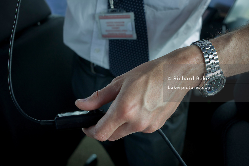 Detail of NATS air traffic controller's hand and radio trigger in control tower at Heathrow airport, London.