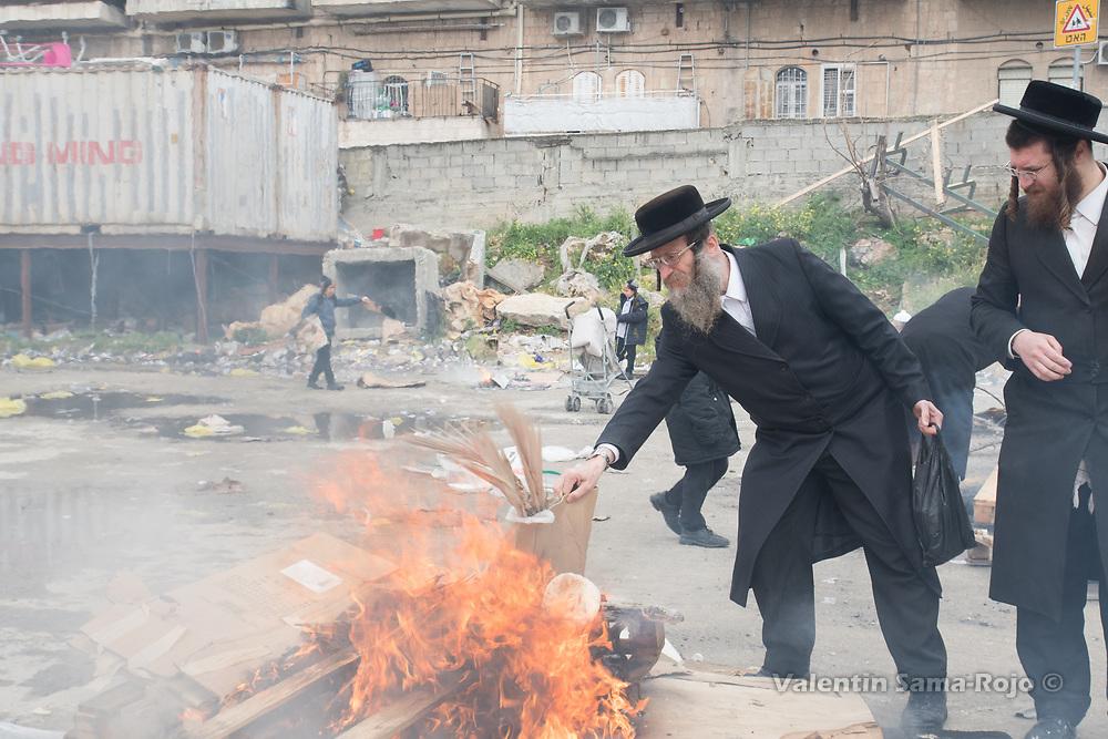 Jerusalem, Israel. 30th March, 2018. A man throwing bread and a palm tree leafs to a bonfire in a street of Mea Shearim neighborhood in Jerusalem. © Valentin Sama-Rojo.