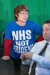"© Licensed to London News Pictures . 12/05/2014 . Manchester , UK . A woman with an "" NHS not trident "" t-shirt in the audience as the leader of the Labour Party , Ed Miliband , delivers a speech on health at the National Squash Centre in Manchester today (Monday 12th May 2014) . Photo credit : Joel Goodman/LNP"