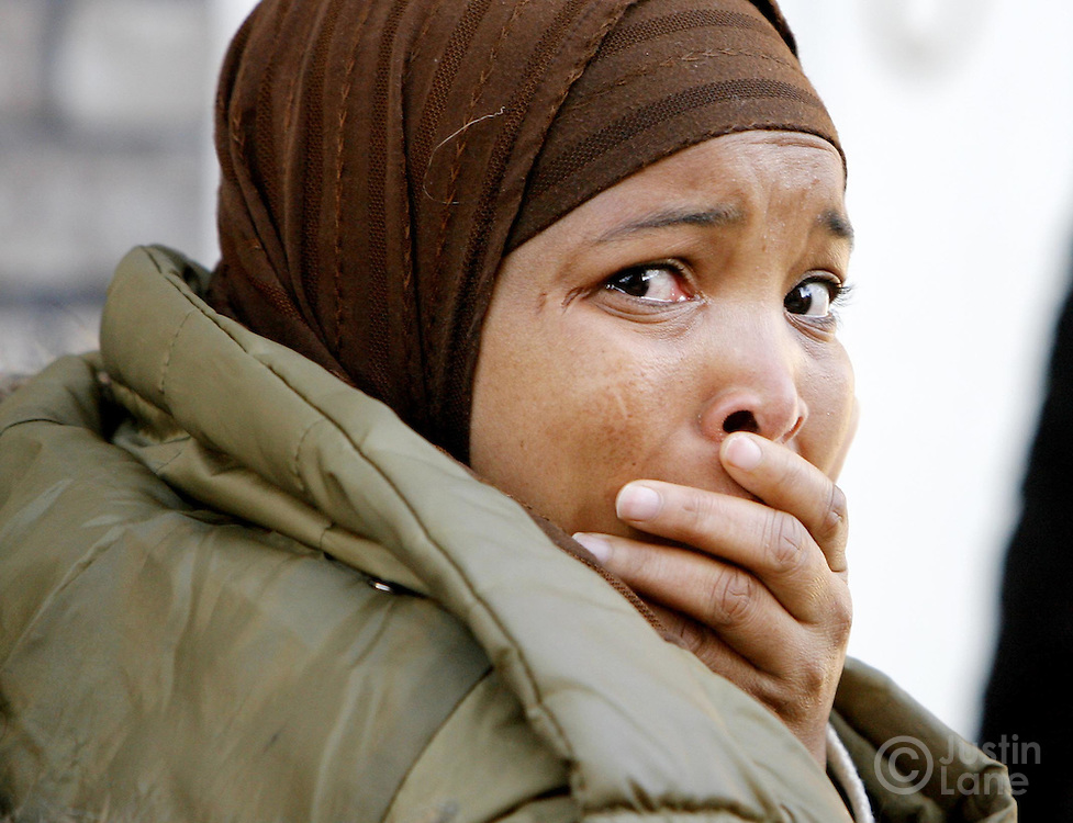 A woman stands outside of a house where 9 people were killed, 8 of them children, in an overnight fire in the Bronx, New York on Thursday 08 March 2007. The two entered a nearby house where members of the family were gathering.