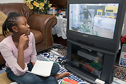Girl sitting on floor in living room watching television while studying for school exams,