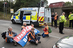 Police officers prepare to arrest Insulate Britain climate activists who had been blocking a slip road from the M25, causing a long tailback on the motorway, as part of a new campaign intended to push the UK government to make significant legislative change to start lowering emissions on 13th September 2021 in Godstone, United Kingdom. The activists, who wrote to Prime Minister Boris Johnson on 13th August, are demanding that the government immediately promises both to fully fund and ensure the insulation of all social housing in Britain by 2025 and to produce within four months a legally binding national plan to fully fund and ensure the full low-energy and low-carbon whole-house retrofit, with no externalised costs, of all homes in Britain by 2030 as part of a just transition to full decarbonisation of all parts of society and the economy.