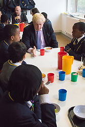 Michaela Community School, Wembley, London, June 23rd 2015. Mayor of London Boris Johnson visits the Michaela Community School, a Free School in Wembley that started taking students in September2014 after battling a certain amount of resistance from locals and unions. During the visit Head Teacher Katharine Birbalsingh took the Mayor on a tour of the school before he participated in a history lesson, prior to sitting down with pupils for brunch. PICTURED: Mayor Boris Johnson enjoys a conversation over brunch with some of the school's pupils.