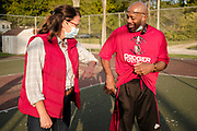 18 SEPTEMBER 2020 - FT. DODGE, IOWA: THERESA GREENFIELD (left, red vest) greets an Iowa voter with an elbow bump in H.C. Meriwether Park in Ft. Dodge. Greenfield, the Democratic candidate for US Senate, visited a National Black Voter Day voter registration event in Ft. Dodge, about 100 miles north of Des Moines. Greenfield is running against incumbent US Senator Joni Ernst, a Republican.       PHOTO BY JACK KURTZ