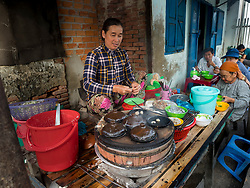 Asia, Vietnam, Mui Ne. Woman cooking and serving traditional Banh Xeo pancakes in street stall