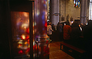Colours from stained glass windows play on a pillar during Mass held in a local rural Catholic church, on 15th October 1997, in Neubourg, Normandy, France.