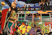 Reveler with Magic Bus at Burning Man. Burning Man is a performance art festival known for art, drugs and sex. It takes place annually in the Black Rock Desert near Gerlach, Nevada, USA..Painted bus in the desert, Burning Man Festival, Black Rock Desert, Nevada. (1998).