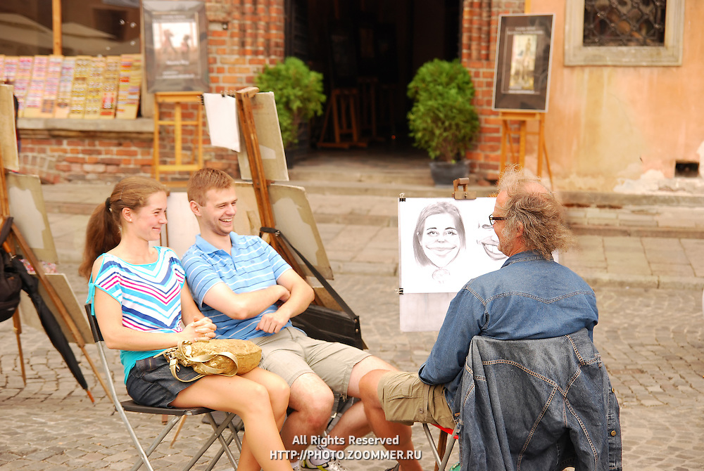 Artist makes a caricature with smiling couple in Warsaw