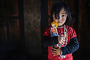 Young girl holding a doll inside the monastery kitchen, Tamshing Goemba, Jakar, Bhutan