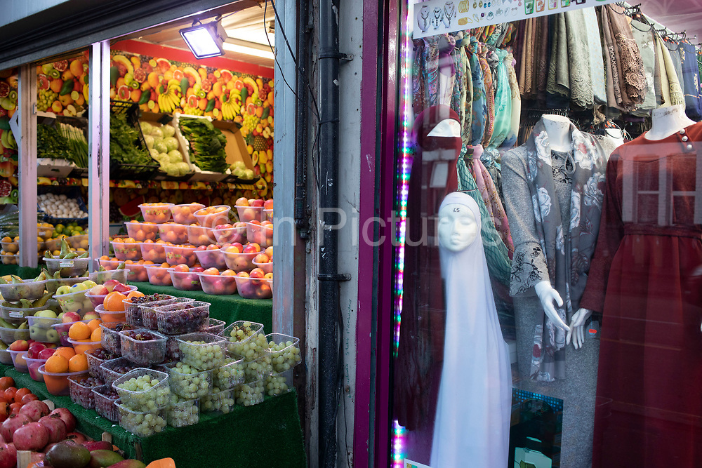 Fruit and vegetable shop next to an Asian womens clothing shop in Leytonstone in East London, United Kingdom. Leytonstone is an area of East London, and part of the London Borough of Waltham Forest.