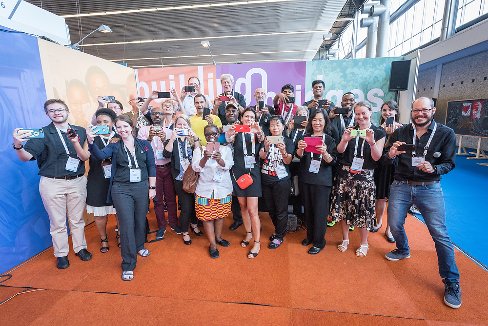 26 July 2018, Amsterdam, the Netherlands: Participants gather for a Thursdays in Black photo after a workshop on how to strengthen your story-telling ability and, incidentally, how to take good photos, led by Kara Eberle and Matt Hackworth from IMA World Health, in the Interfaith Networking Zone at AIDS 2018. As a playful way of making the group photo more lively, they have turned the scenario around, pretending to all take a photo of the photographer, instead of having their own photo taken.