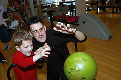 Father and son play ten pin bowling at arcade Yorkshire UK MR