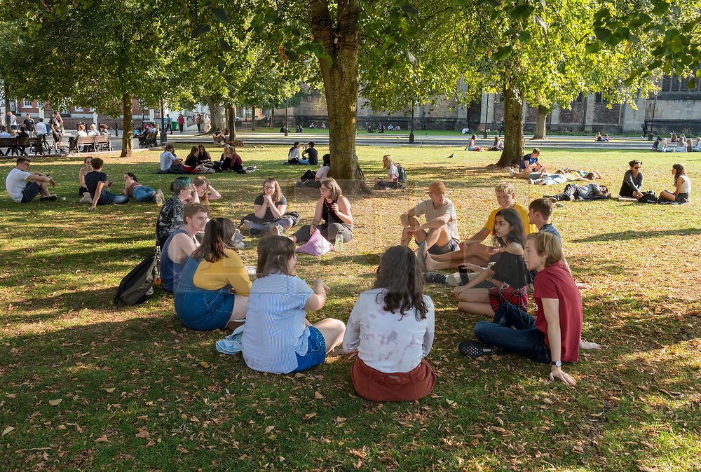 """© Licensed to London News Pictures; 21/09/2020; Bristol, UK. A group of 13 young people sit on College Green. Groups of people, some more than six in number, enjoy the sunshine and hot weather on the last official day of summer in Bristol city centre, amid concerns about a second wave of the covid-19 coronavirus pandemic across the UK, with many areas going into local lock down. From Monday 14 September it was illegal to meet up socially in groups of more than six people, known as the """"Rule of Six"""", in order to try and contain the spread of the covid-19 coronavirus pandemic, and police have said they will enforce the law with fixed penalty notices which will increase for repeat offenders. Photo credit: Simon Chapman/LNP."""