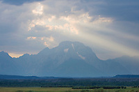 Evening sun rays break through the clouds over Mount Moran, Grand Teton National Park, Wyoming