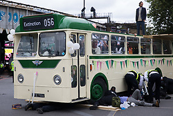 London, UK. 31st August, 2021. Police officers work to remove Extinction Rebellion activists who used a vintage bus as a base to block a road junction to the south of London Bridge on the ninth day of their Impossible Rebellion protests. Extinction Rebellion are calling on the UK government to cease all new fossil fuel investment with immediate effect.